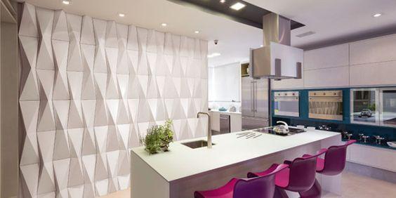 Cozinha elegante e moderna, com uma imponente ilha no meio, cadeiras roxas e detalhe do armário em turquesa. Parede com revestimento 3D branca e luzes em sua direção.