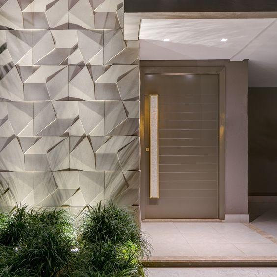 53 ambientes com revestimentos 3D para te inspirar Fachada de imóvel com revestimento 3D na parede, luzes no jardim direcionadas para parede e do lado direito uma porta sofisticada de cor neutra.