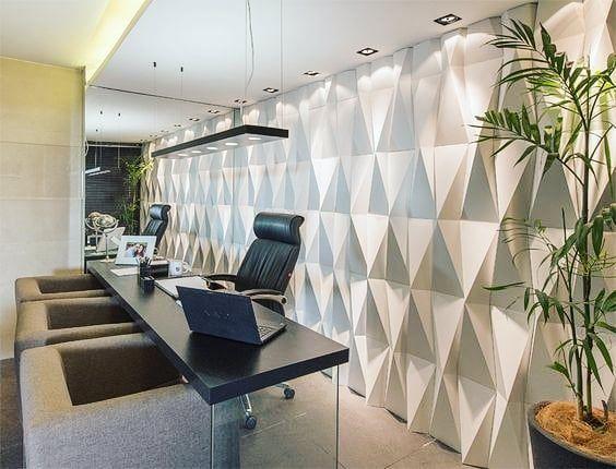 escritório com revestimento 3D, que traz volume, na parede. Mesa retangular com pernas de vidro e poltronas.