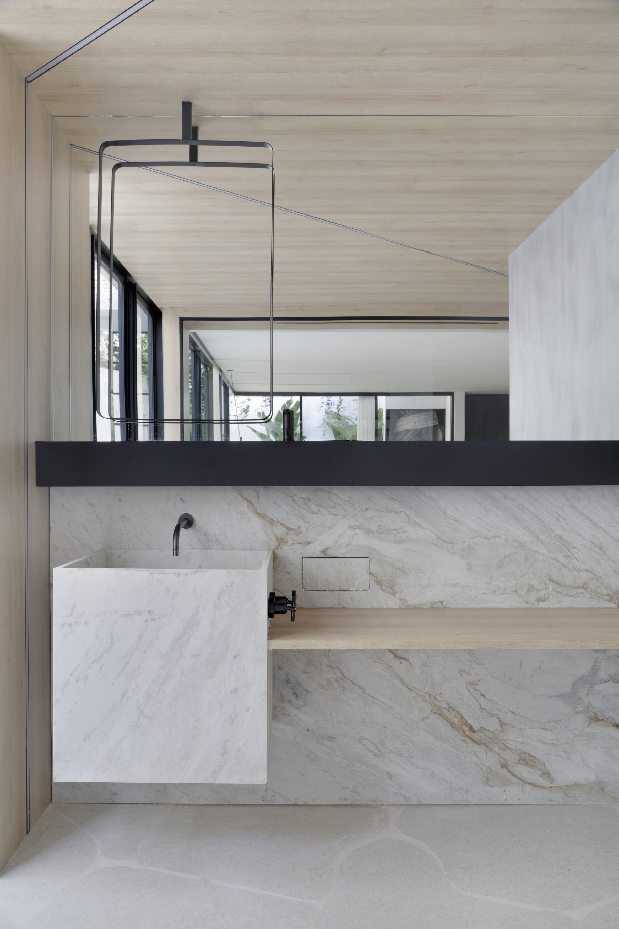 Casa Conecta: Ticiane Lima, CASACOR SP 2019.  Lavabo de mármore, torneira e registro em cor preta,bancada de madeira e parede com revestimento em mármore, espelho horizontal e piso em formato de rochas.