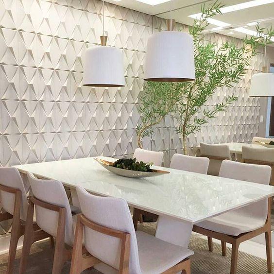 Sala de jantar com revestimento branco 3D junto a uma parede de vidro que traz uma sensação de continuidade. mesa de granito, cadeiras brancas de madeira e luminárias.