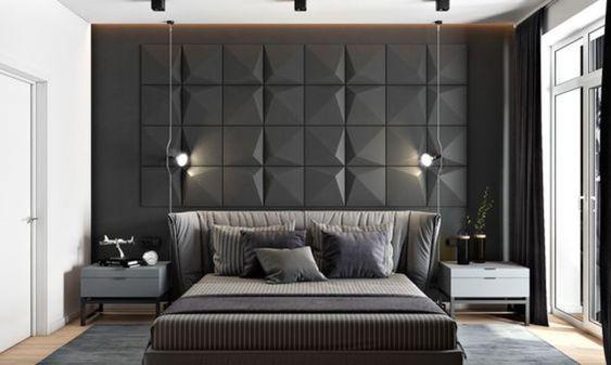 """Quarto com decoração moderna mescla tons escuros com branco. cama espaçosa, criados mudos de cores diferentes, tapete cinza e revestimento 3d na parede com efeito """"acolchoado""""."""