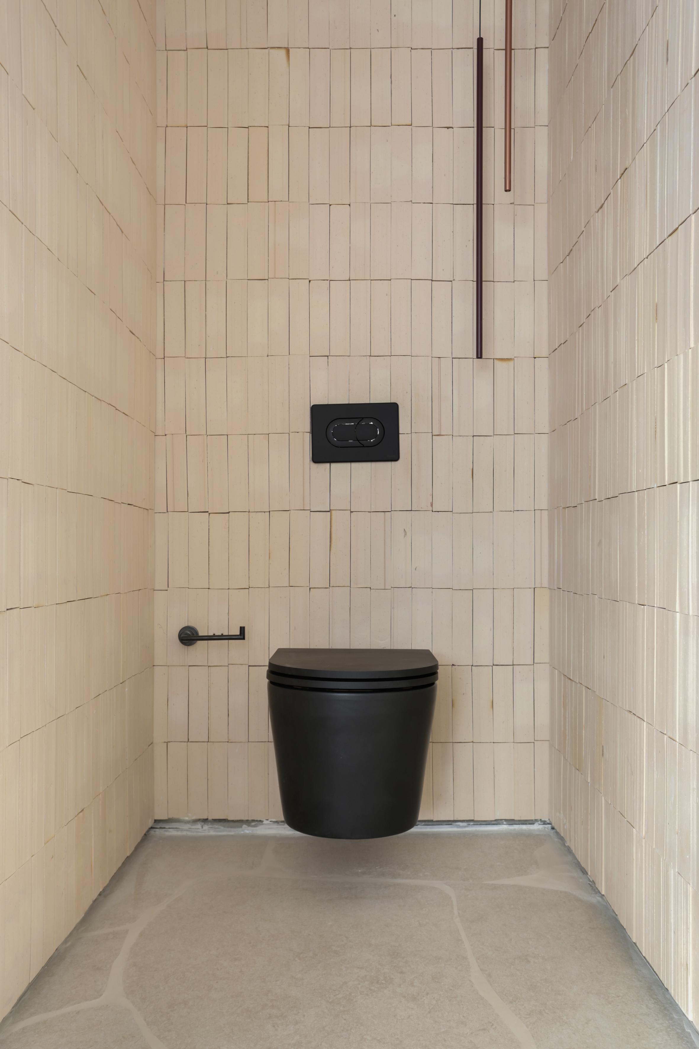 Casa Conecta: Ticiane Lima, CASACOR SP 2019. área intima do banheiro. Sanitário preto, azulejo na cor beje e piso em formato de rocha.