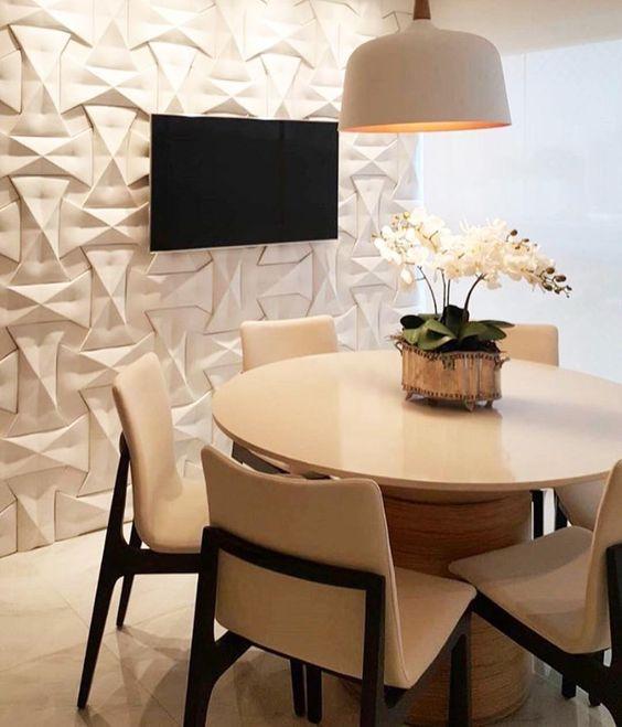 Varanda com decór clássico; mesa redonda e cadeiras em tom claro. Parede com revestimento 3D com detalhe que se assemelha a uma trama. Uma enorme luminária sob a mesa.