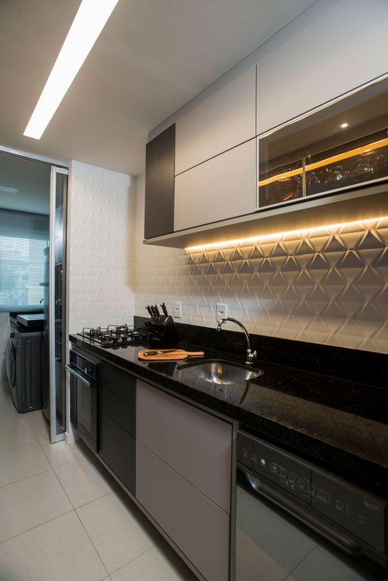 cozinha com estilo clean integrada com lavanderia. Pia de mármore, gabinete cinza&preto e armário branco. Parede com revestimento 3D discreto.