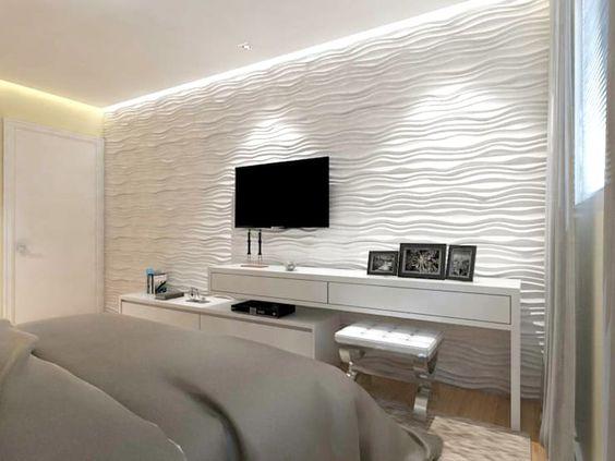 Quarto com tons claro; cama grande, um armário rente à parede e uma parede com revestimento 3D de textura ondular.