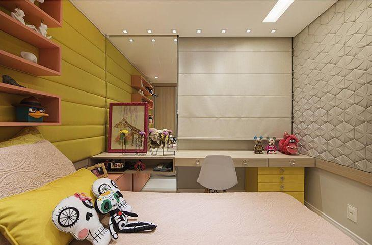 Quarto com estilo adolescente, a cor amarela está presente na parede lateral, almofadas e um pequeno armário. Escrivaninha no fundo do quarto junto com cortina persiana e espelho. Parede da direita com revestimento 3D floral.  Parede com revestimento 3D.