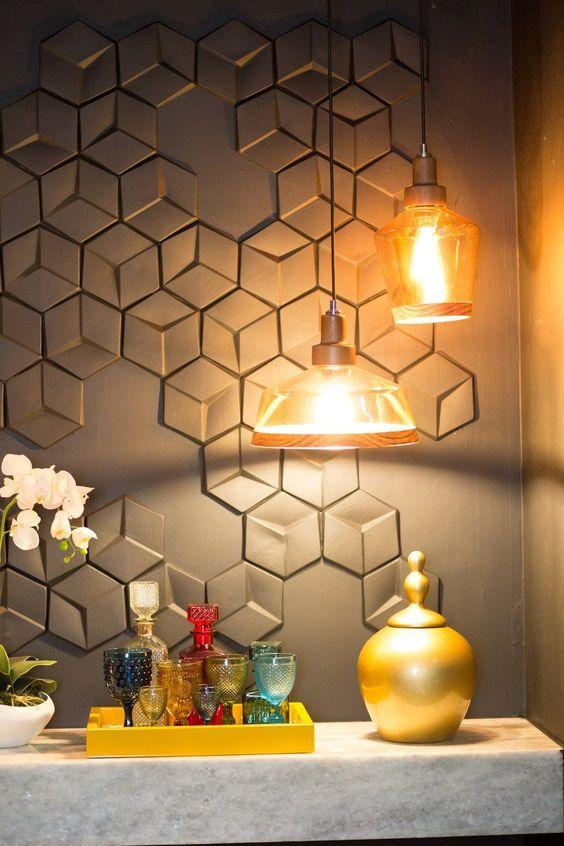 Bar com bancada de mármore rente a mesa e uma luminária sob esta mesa. Parede com revestimento 3D em padronagem irregular na mesma cor da parede.
