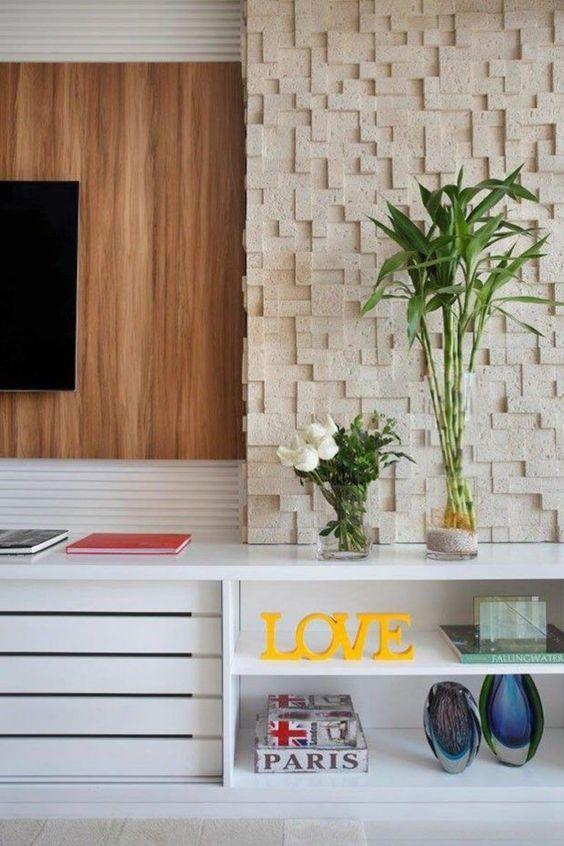 53 ambientes com revestimentos 3D para te inspirar rack branco, parede com revestimento 3D com aparência de pedra natural e painel de madeira.