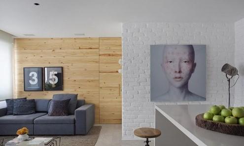 Estilo industrial. Apartamento com sala de estar e jantar integradas. Parede com tijolinhos pintados de branco, parede da sala de jantar com revestimento em madeira, balcão de mármore, sofá, quadros, tapete e mesa de centro.