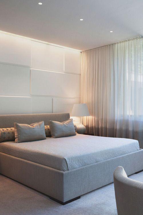 Quarto minimalista, cama espaçosa, cortina longa e abajur tradicional. A cabeceira da cama com revestimento branco 3D.  Parede com revestimento 3D.