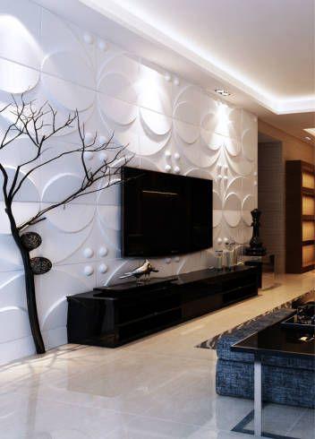 Sala de estar com rack preto e outros móveis em cor preta. Parede com revestimento 3D branca com formas circulares.