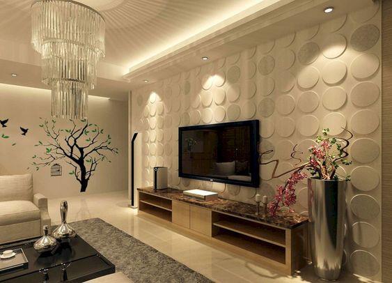 Sala de estar elegante. mesinha de centro preta, sofá beje, lustre luxuoso, tapete veludado, rack de madeira e cachepô com plantas. Parede rente ao rack tem revestimento 3D com formas circulares. Parede com revestimento 3D.