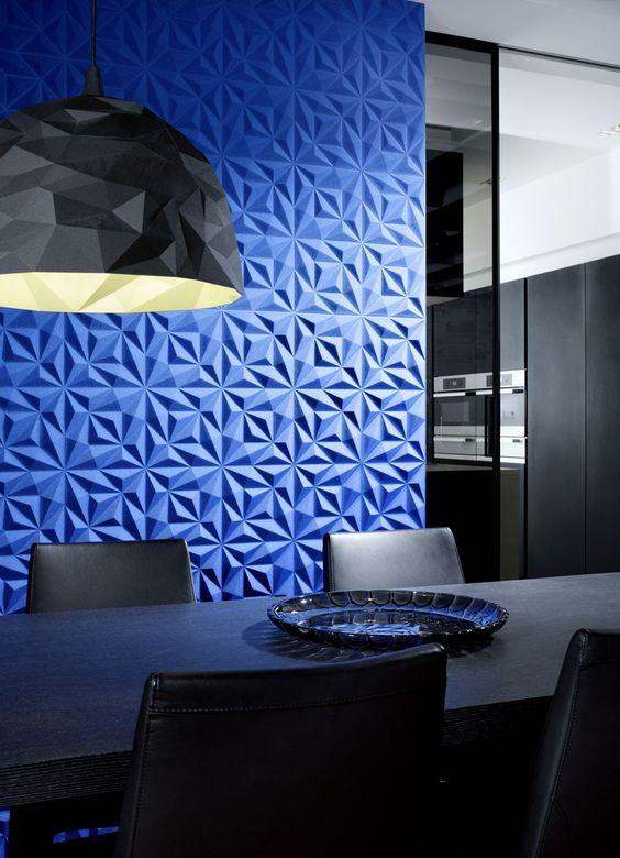 Sala de jantar com tons sóbrios contrapondo a parede de tom azul. mesa preta, cadeiras de couro, luminária e parede com revestimento 3D azul.