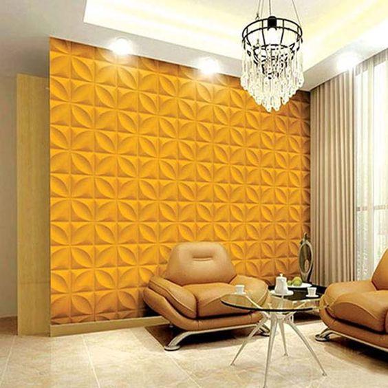 Sala de estar com poltronas de couro, mesinha de vidro e lustre sofisticado. Parede amarela com revestimento 3D. Parede com revestimento 3D.