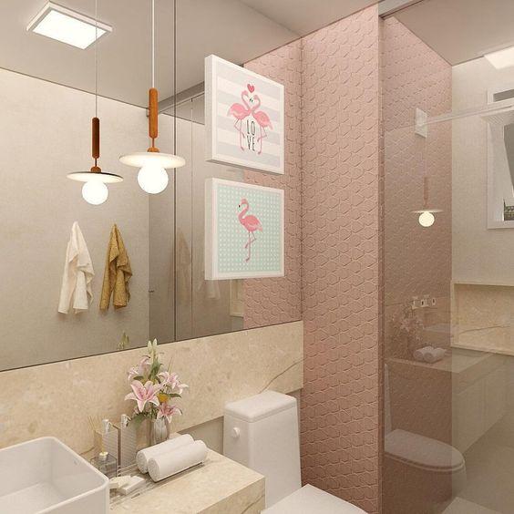 Banheiro com revestimento 3D rosa, no box. Pia de mármore, espelho grande e sanitário branco.