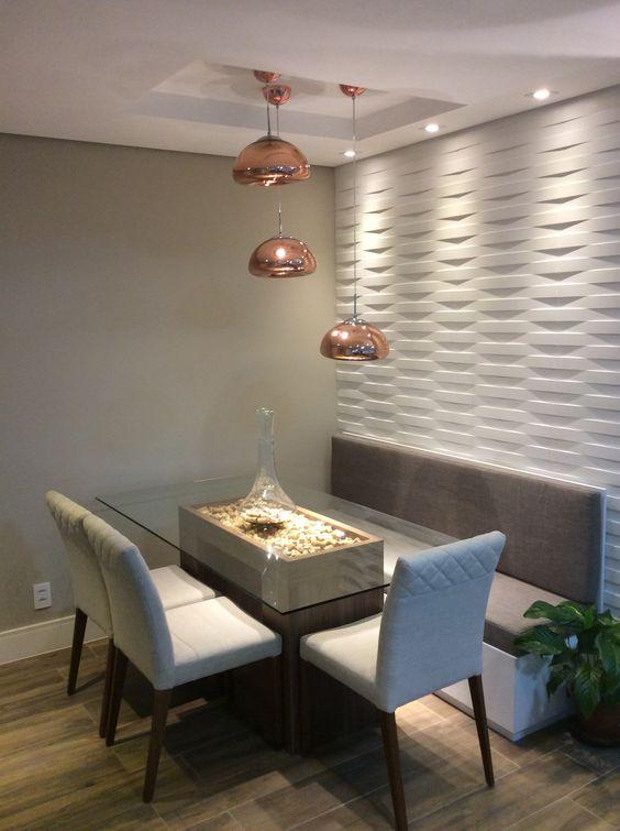 Sala de jantar com mesa de vidro, cadeiras acolchoadas, assento rente a parede e três luminárias. Parede com revestimento 3D, branca, que simula uma trama.