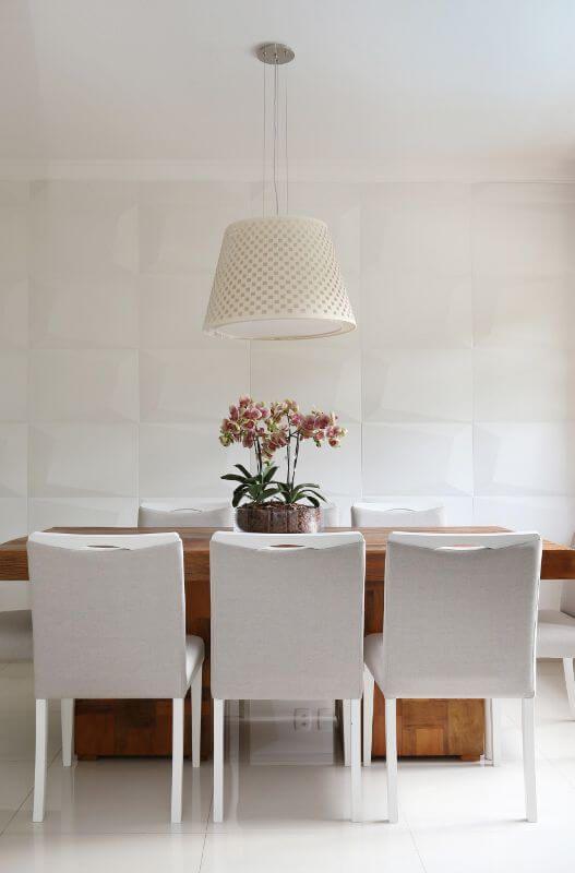 Sala de jantar com mesa de madeira, cadeiras brancas, luminária tradicional e parede com revestimento 3D em forma de grandes placas com volume.