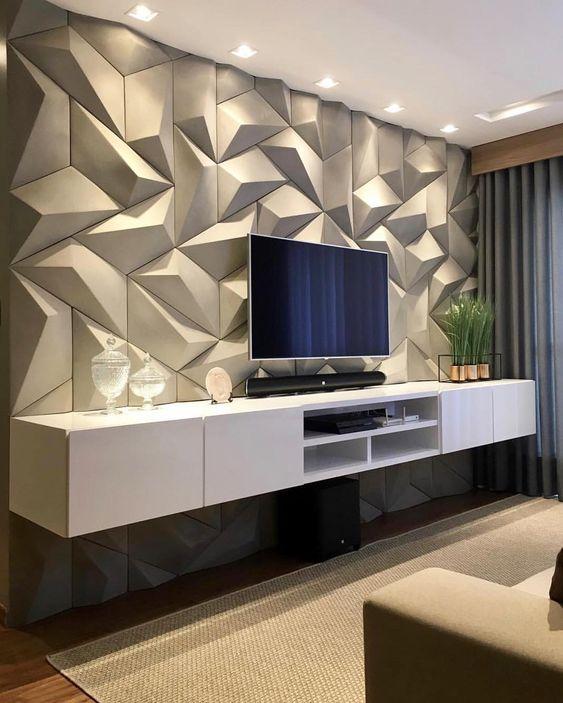 Sala de estar; rack branco, tapete, cortina comprida e objetos decorativos. Parede com revestimento 3D com volumetria.