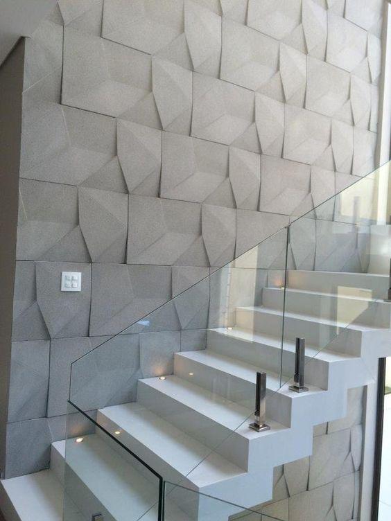 53 ambientes com revestimentos 3D para te inspirar Parede de acesso a escada com revestimento 3D, escada branca com luzes na lateral e o guarda-corpo de vidro.