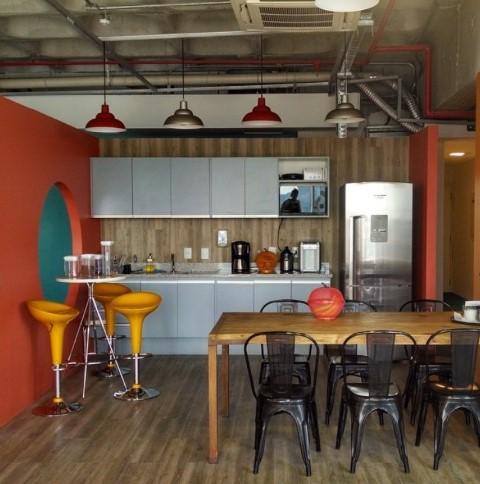 Estilo industrial. Cozinha integrada com sala de jantar. paredes e piso com revestimento de madeira corrida, amarios em tom azul, mesa de madeira, cadeiras pretas e luminárias de teto.