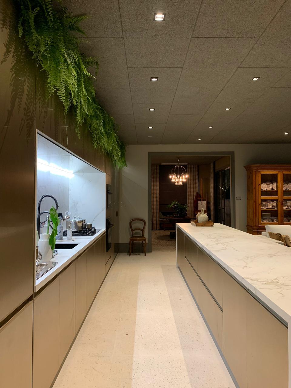 Living do Restaurante by Gustavo Paschoalim. CASACOR SP 2019. BADEBEC. Cozinha dourada, Bancada em ilha, itens garimpados e piso com tons claros.