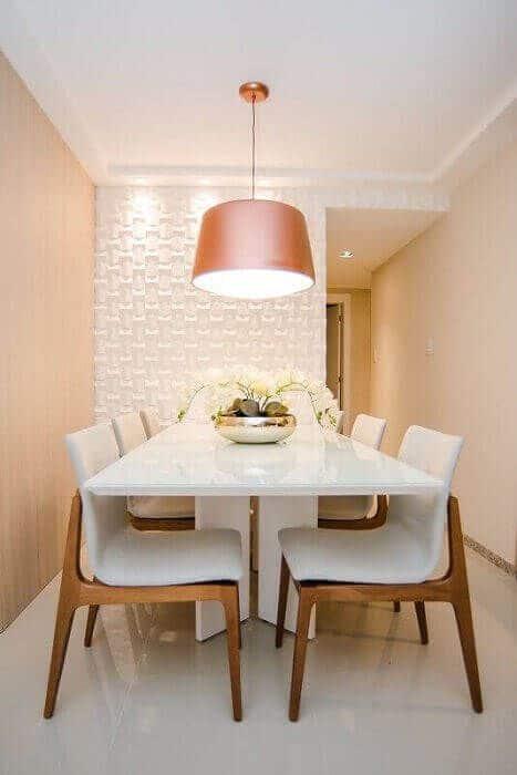 Sala de jantar com mesa branca, cadeiras brancas com pernas de madeira, paredes laterais bejes, e luminária beje. Ao fundo, parede com revestimento 3D branca.
