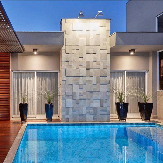 Área externa com piscina, portas de vidro e vasos de plantas. Parede com revestimento 3D semelhante a pedras.