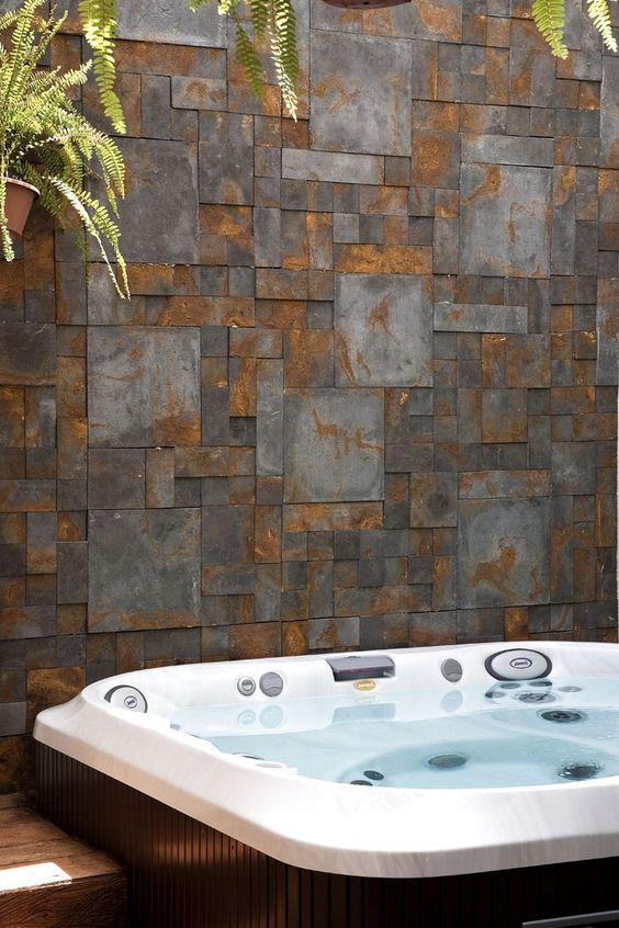 Área externa com banheira de hidromassagem revestida com madeira. Ao fundo, uma parede com revestimento 3D de efeito oxidado. E samambaias.