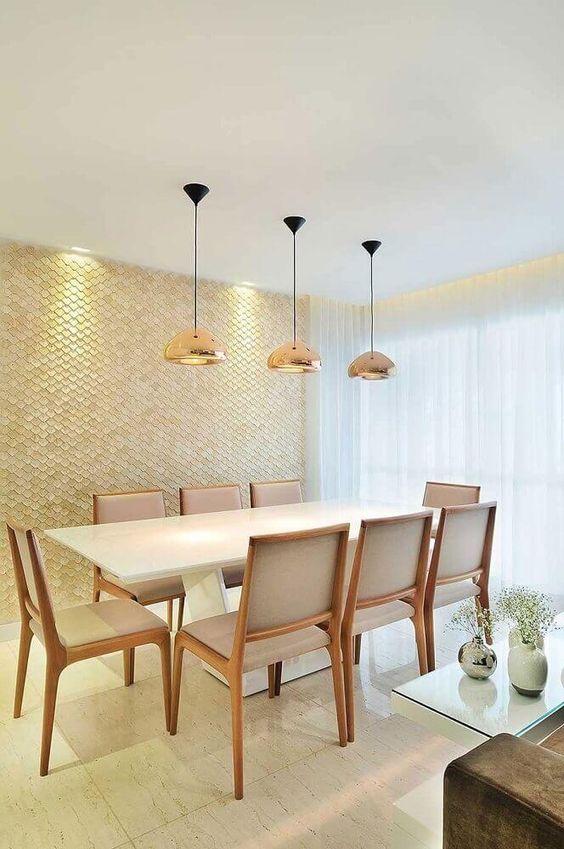 Sala de jantar com mesa de mármore, cadeiras de madeira, luminárias douradas e parede com revestimento 3D de efeito escama de peixe. Ao fundo, uma longa cortina branca.