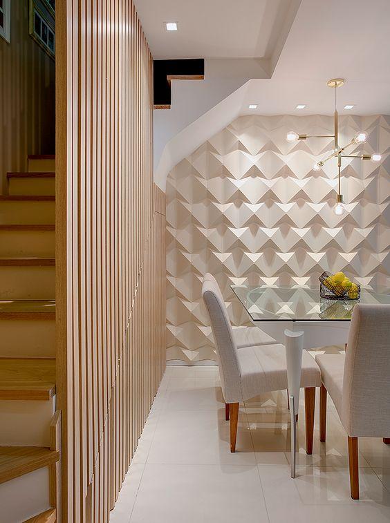 53 ambientes com revestimentos 3D para te inspirar Sala de jantar com acesso a escada no lado esquerdo, decoração clean, parede  do fundo com revestimento 3D, mesa retangular de vidro com pernas de metal, cadeiras estofadas com pernas de madeira, piso revestido com porcelanato branco e painel de madeira ao lado da escada.