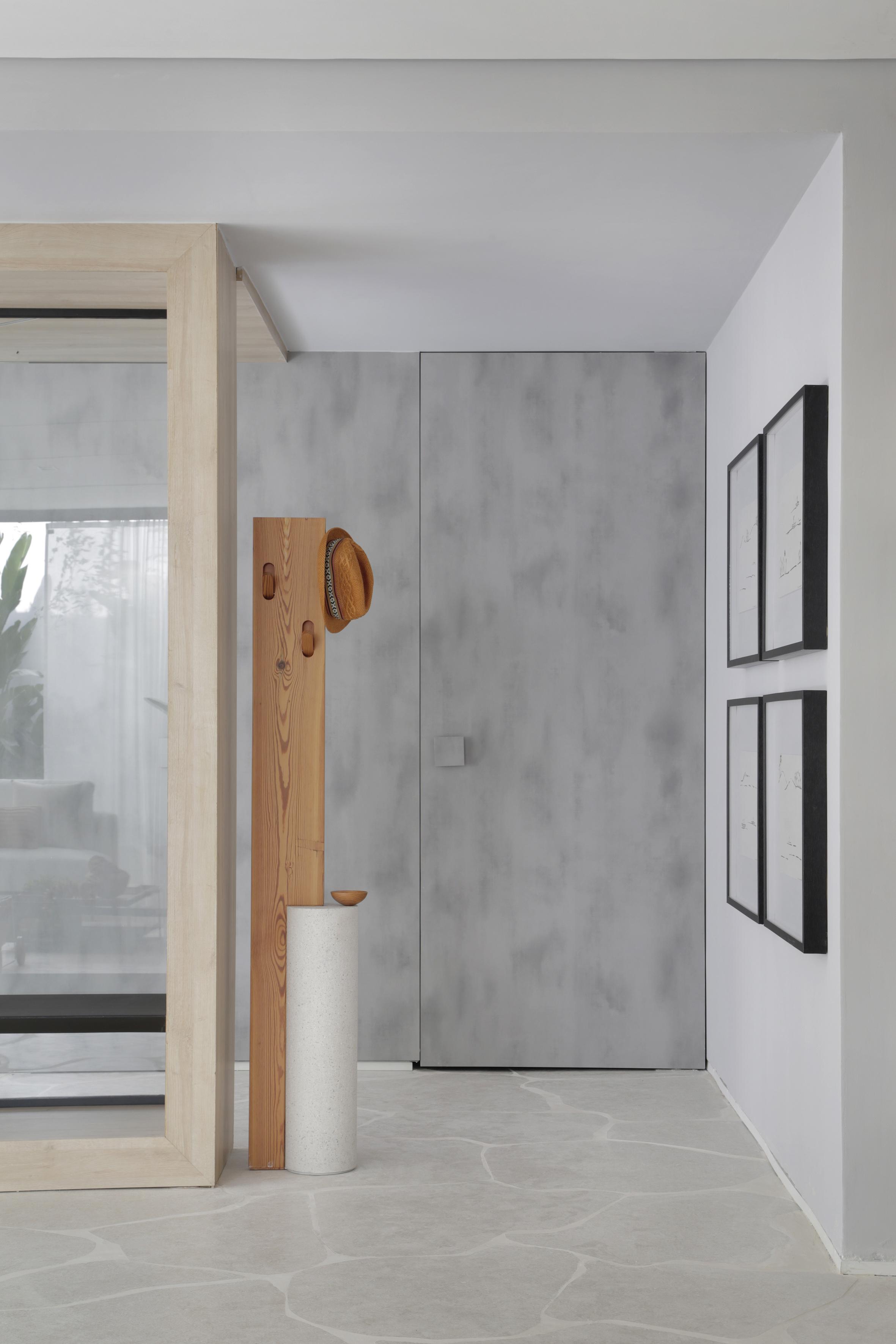 Living e banheiros separados por uma parede de vidro, piso em formato de rocha, cabideiro com chapéu e quadros de decoração.  Casa Conecta: Ticiane Lima, CASACOR SP 2019.
