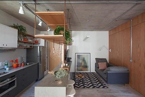 Estilo industrial. Cozinha integrada com sala de estar. espaço reduzido. tubulações aparentes, teto de cimento queimado, balcão em tom cinza, parede com revestimento de madeira em cor carvalho e piso com revestimento em madeira patina. Prateleiras suspensas no teto.