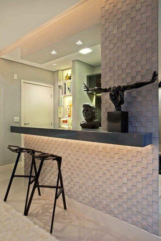 53 ambientes com revestimentos 3D para te inspirar Cozinha com balcão. Parede e balcão com revestimento 3D em formas geométricas e cinza, decoração com cor preta e bancos de metal pretos.