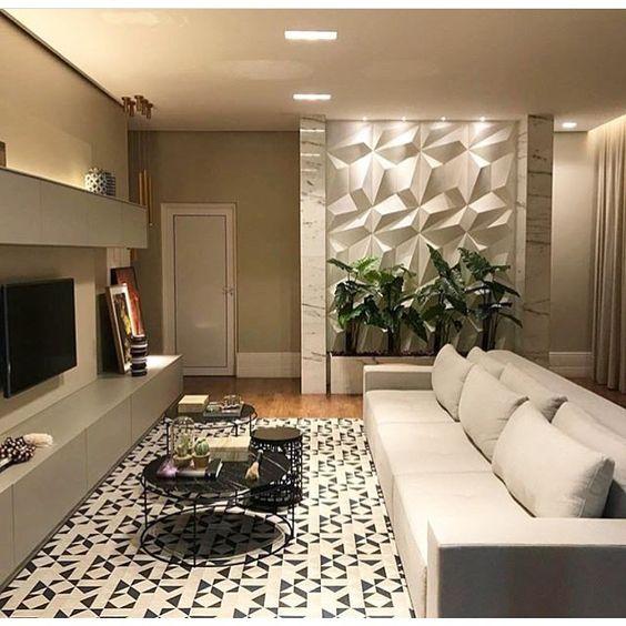 53 ambientes com revestimentos 3D para te inspirar Sala de estar com cores neutras, sofá branco, rack, tapete branco com detalhes pretos, mesinhas redondas pretas e parede de fundo com revestimento 3D e iluminação.