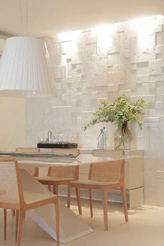 53 ambientes com revestimentos 3D para te inspirar Sala de jantar com decoração clássica, cadeiras vintage, mesa de vidro, lustre branco em forma de cone, uma mesinha de canto ao fundo e parede com revestimento rustico de cor branca.