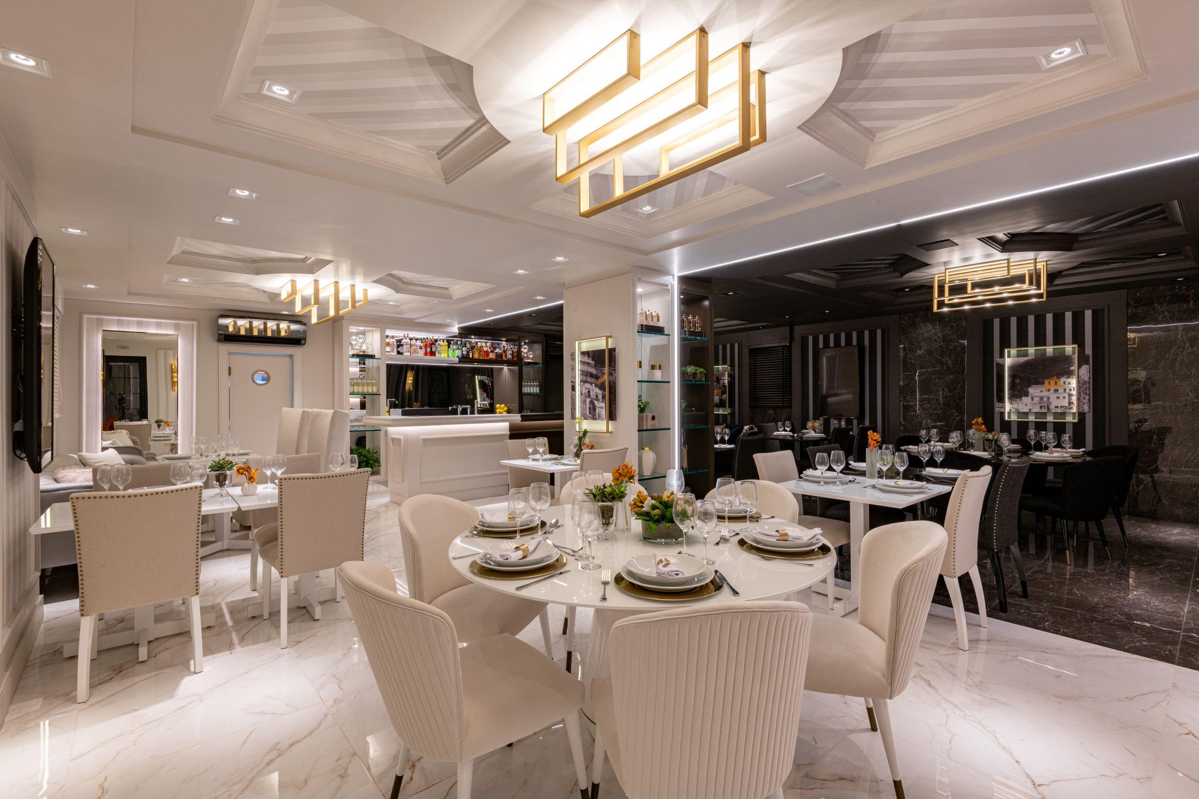"""Restaurante Limone, CASACOR São Paulo 2019, Habitat Projetos Inteligentes. Restaurante com conceito de dualidade. """"Lado dia"""", porcelanato que imita mármore branco, cadeiras clássicas brancas, mesas de mármore branco e teto de gesso."""