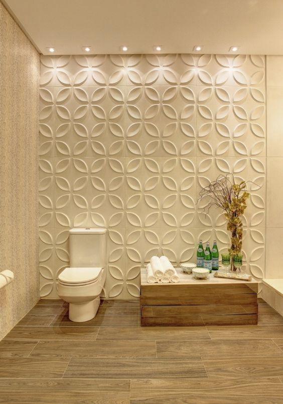 53 ambientes com revestimentos 3D para te inspirar Banheiro com decoração neutra, sanitário branco, mesinha de madeira, piso revestido com porcelanato que imita madeira e parede com revestimento branco 3D adesivo