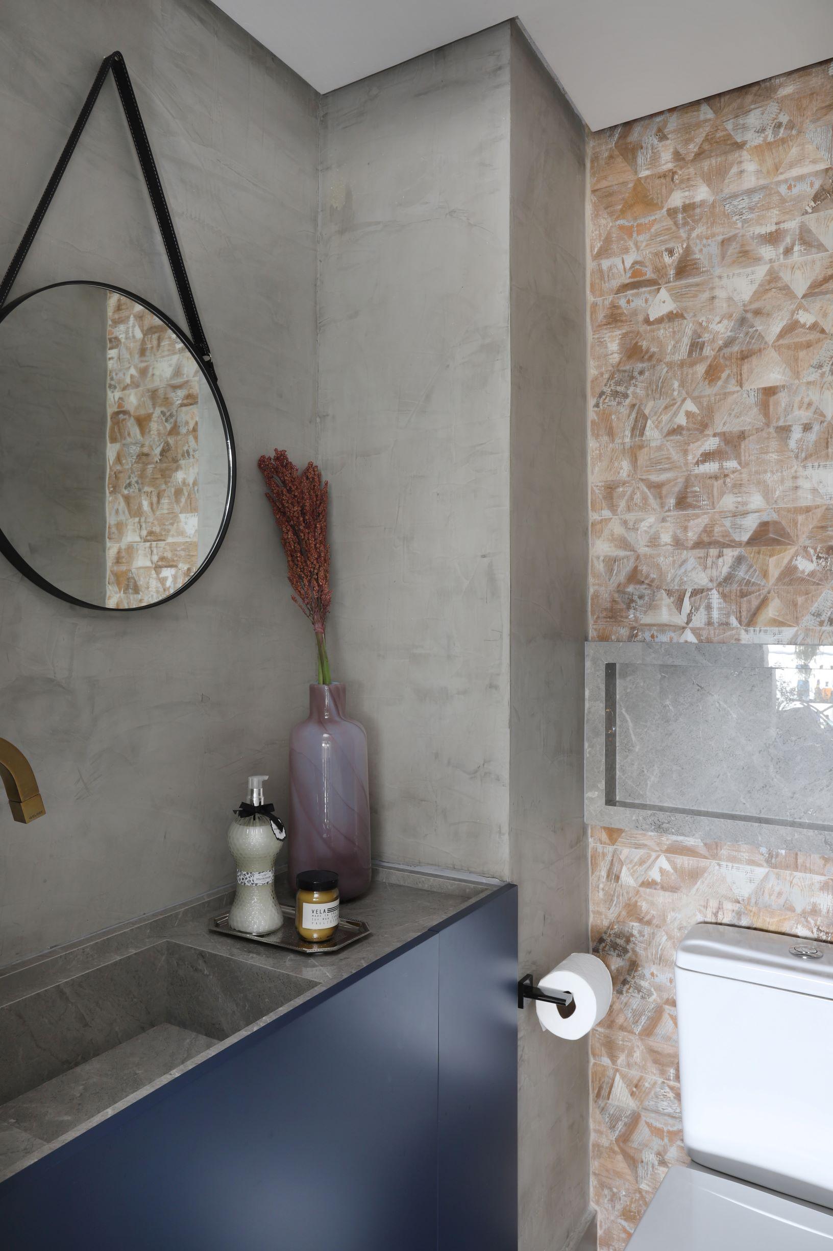 Banheiro com parede de cimento queimado e bancada de porcelanato.