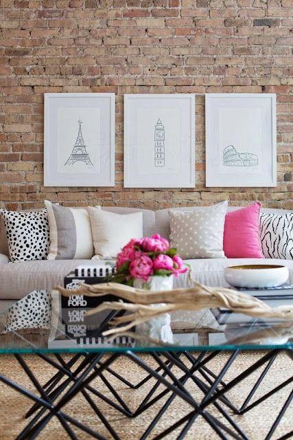Living com tijolinhos aparentes, quadros na parede e sofá.