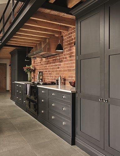 Cozinha com parede de tijolinhos, piso superior com estrutura exposta de madeira e armários pretos no estilo provençal.