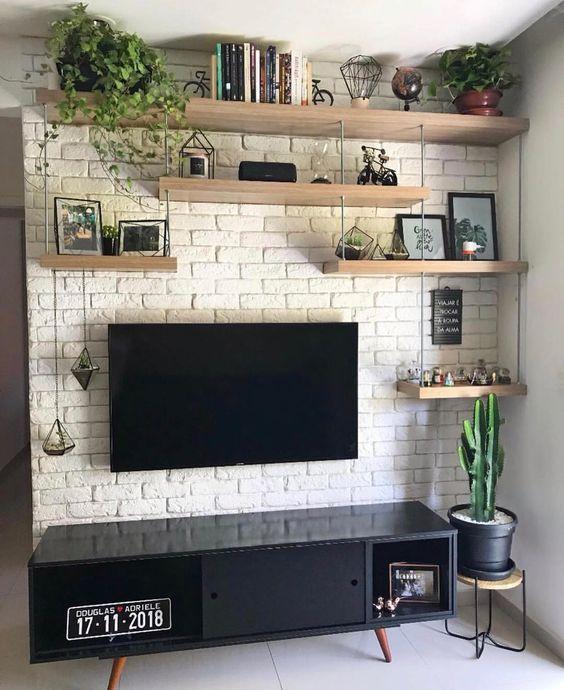 Sala de estar com prateleiras suspensas e tijolinhos aparentes com pintura clara. Plantas na decoração