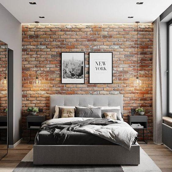 Quarto com tijolinhos aparentes em tonalidade irregular, criados mudos, teto com rebaixamento de gesso, Luminárias de teto nas laterias e dois quadros na parede.