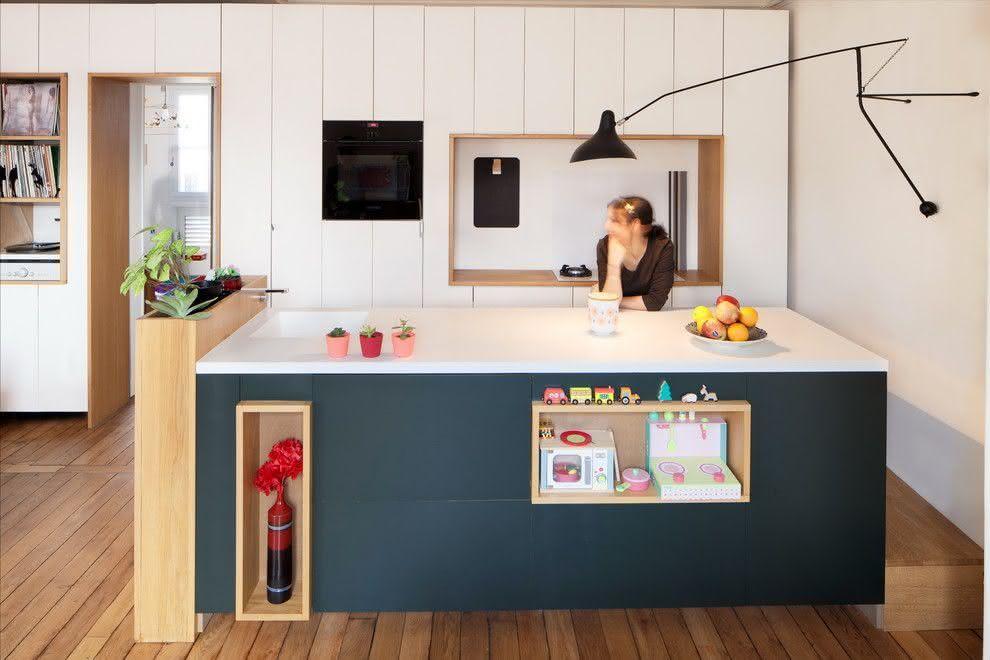 Cozinha escandinava, com nichos na ilha para decoração e armazenar atividades das crianças. Piso com revestimento de madeira, luminária de parede e armários brancos.