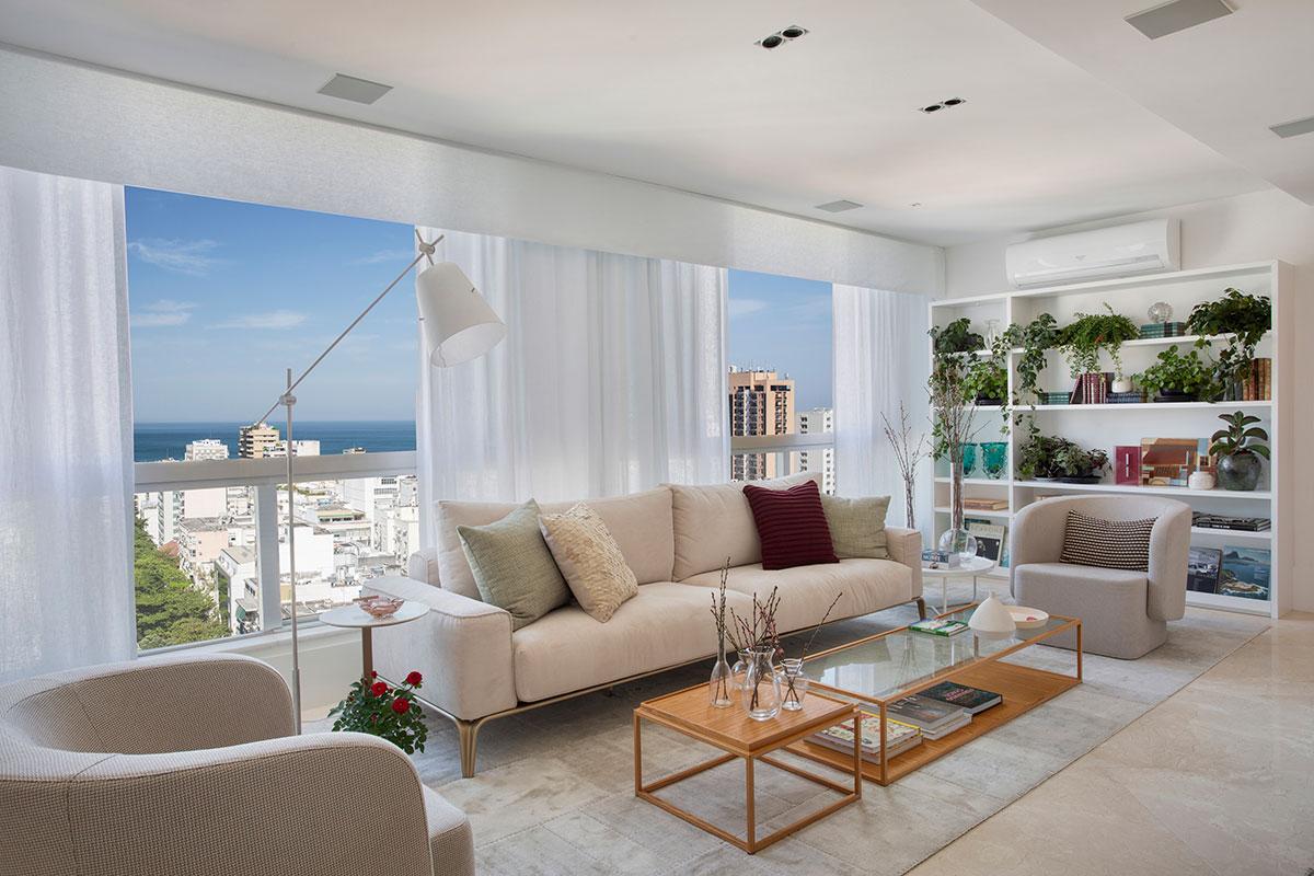 Sala de estar de apartamento com grandes janelas que permitem a entrada de luz natural. Decoração clean com revestimentos em tom claro. Estilo Contemporâneo
