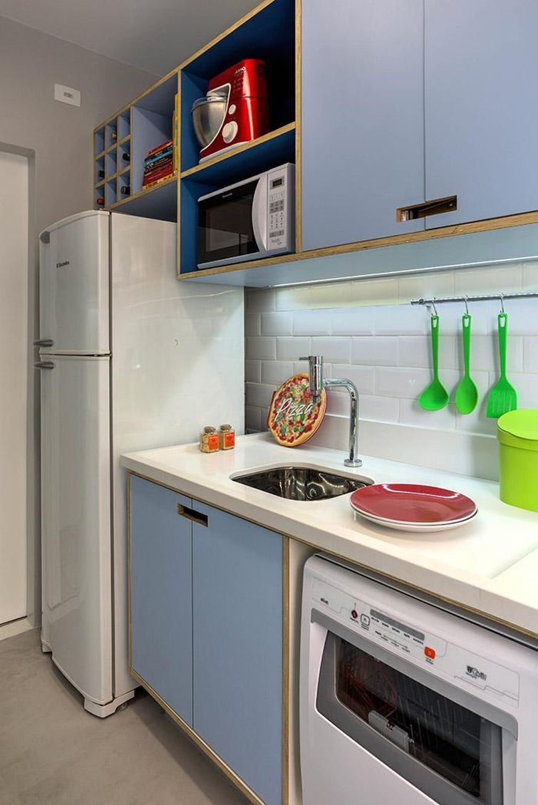 Cozinha pequena com revestimento de metrô, armários na cor azul pastel e sobre a geladeira uma adega.