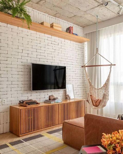 Sala de estar com tijolinhos aparentes brancos, prateleira de madeira clara e teto de concreto.