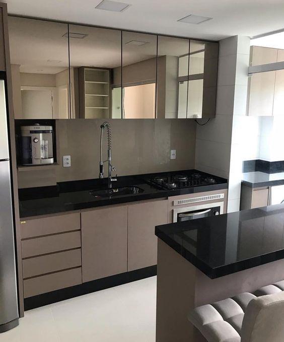 Cozinha pequena com superfícies espelhadas. bancada de porcelanato.