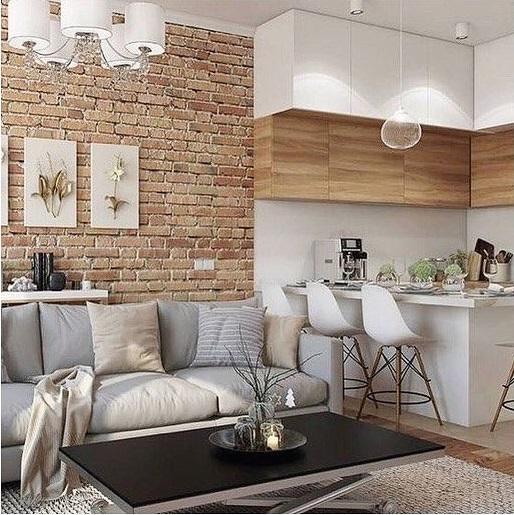 Sala de estar integrada com cozinha. Parede de tijolinhos e armários de madeira clara.
