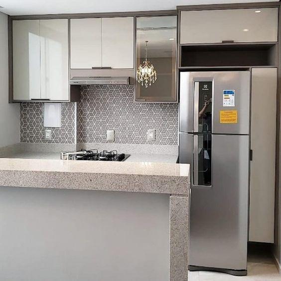 Cozinha pequena com bom aproveitamento de espaço. Parede com revestimento geométrico.